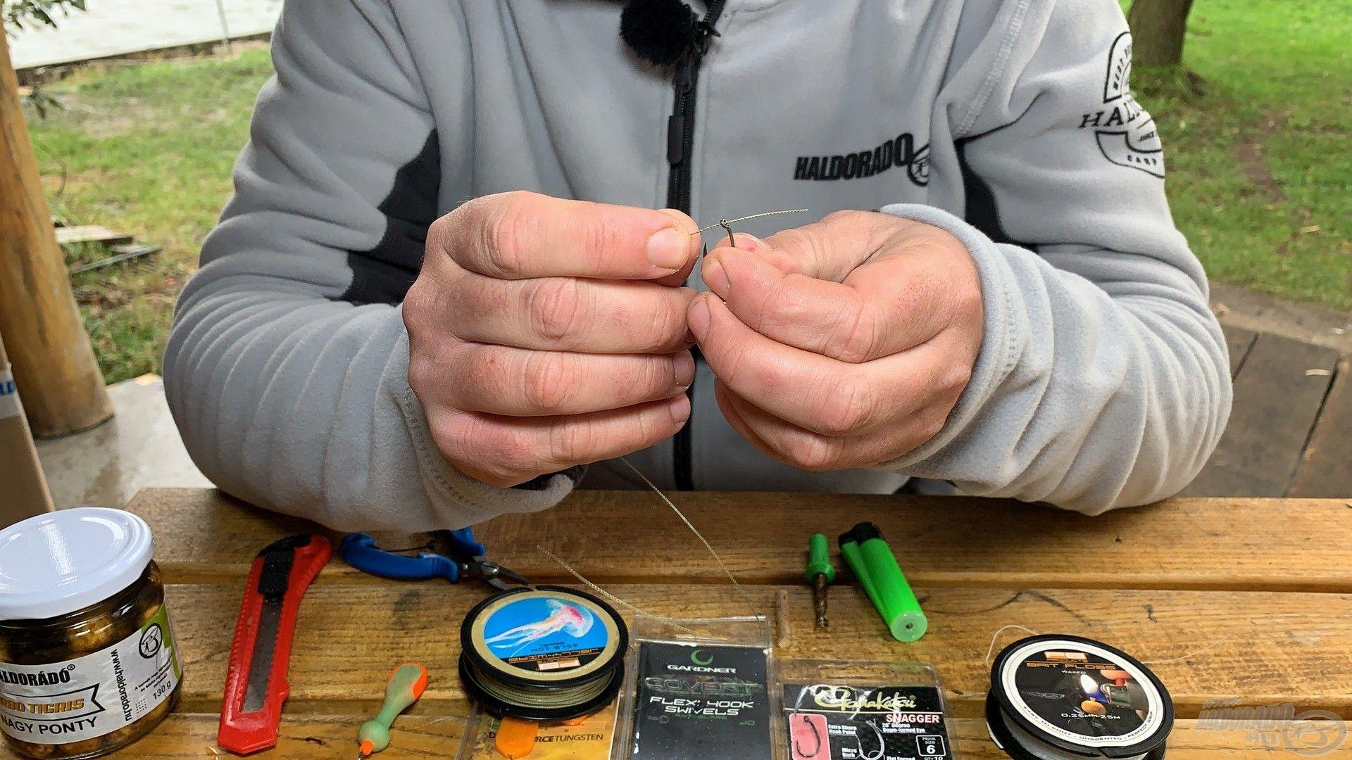 Első lépés, hogy a méretre vágott előkezsinórra csomó nélküli kötéssel rögzítem a kiválasztott horgot
