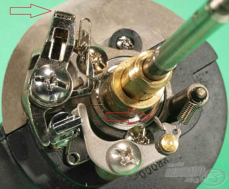 A felső sarokban látható nagy kilincs akad be a rotor belső palástjának fogazatába, a középen jelzett kis rugós pöcök pedig a racsnihangot adja a rotor közepén lévő, apró fogú fogaskeréken. Ezen a képen a kikapcsolt állapot látszik…