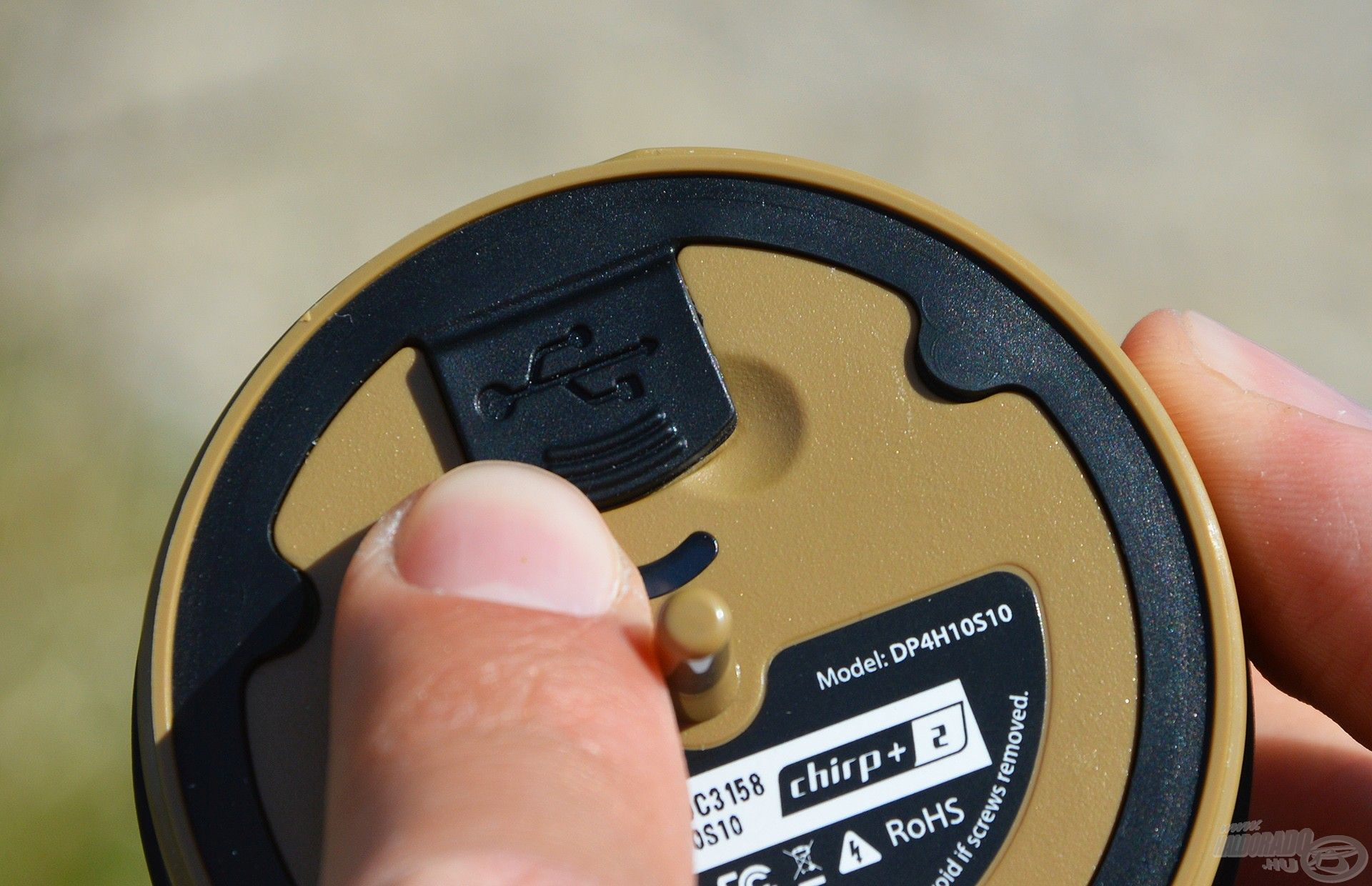Egy gumírozott kis zárónfedél alatt található a töltő csatlakozó