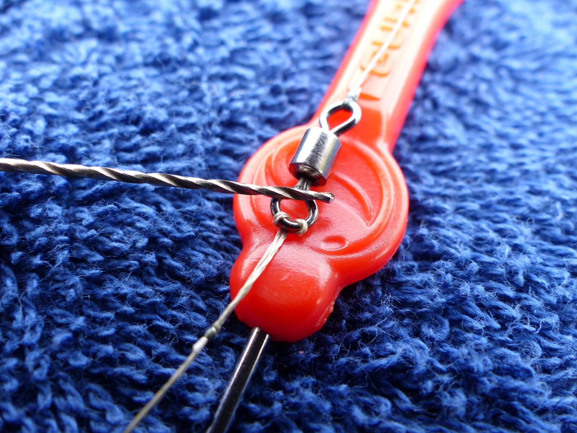 """2. lépés: Egy vékony fűzőtű vagy csalifúró segítségével (akár körömmel óvatosan) a kis hurok két """"szálát"""" ellentétes irányba mozdítva szét kell választani egymástól…"""
