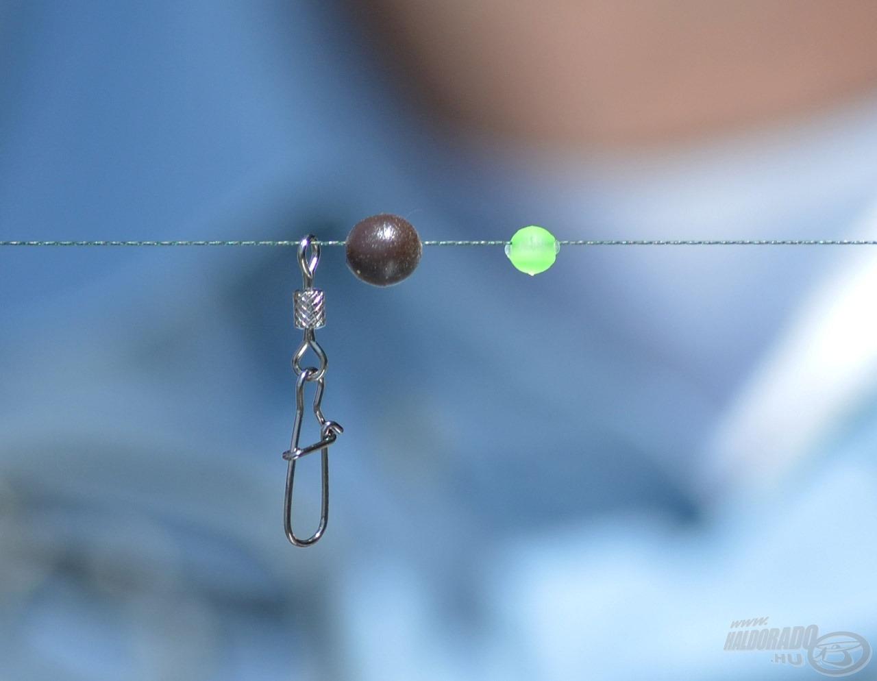 A dobóelőkére az itt látható sorrendben fűzzük fel a karabineres forgót, gumigolyót és műanyag gyöngyöt…