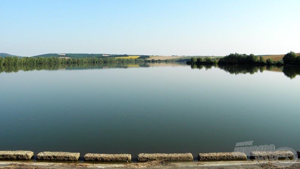 A Sinkár-tó a gátról nézve. Szép nagy vízterület, és nem csak a víz, de a környezet is lenyűgöző. A kép közepénél, a legtávolabbi pont környékén van a bejárat és a halőrház