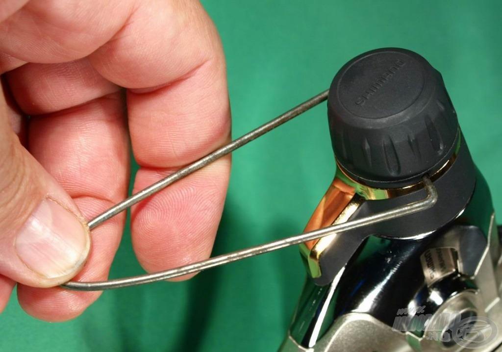 Az arany csík mögött látható két kis bemélyedés lehetővé teszi, hogy házi készítésű (bicikliküllőből hajlított) célszerszámmal rögzítsük a gyűrűt, és letekerhessük róla a kupakot