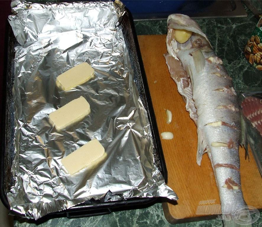 """A tűzdelt, megfelelően besózott süllőt tepsiben sütjük. A sütőedény anyagának függvényében tehetünk a hal alá alufóliát is, némi vajjal vagy margarinnal azonban mindenképpen """"ágyazzunk meg"""" neki"""